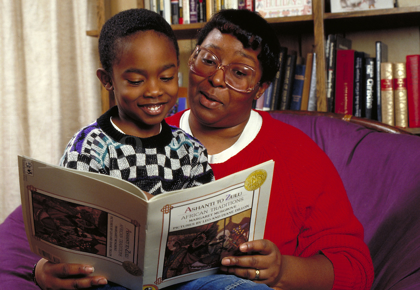 AFRICAN-AMERICAN MOTHER READING TO HER SON ABOUT HIS HERITAGE AT KWANZAA TIME OF YEAR(DECEMBER). AFRICAN-AMERICAN MOTHER AND CHILD. CHICAGO ILLINOIS.