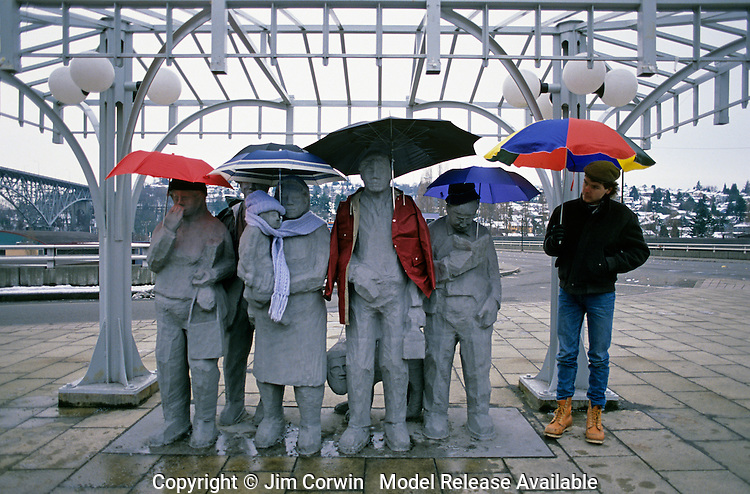 "Fremont statues ""Waiting for the Interurban"" Artist Richard Beyer with umbrellas and jackets with another person waiting for the bus Fremont neighborhood Seattle Washington State USA   MR"