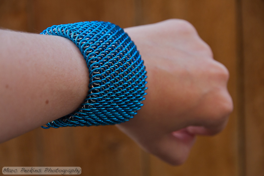 "A blue and silver dragonscale weave maille bracelet seen at an angle on an arm.  It's made from saw cut 18 gauge 1/4"" ID blue anodized aluminum rings and saw cut 19 gauge 5/32"" ID bright aluminum rings.  The clasp is a gunmental plated slide clasp.   Handmade by Michelle."