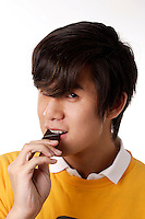 montreal  (QC) CANADA - Sept  2009 - model released photo of an asian teenage male eating dark chocolate