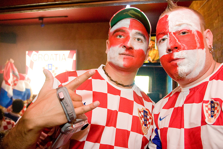 Croatia fans Matty Goshen, right, and Sino Babic cheer on their team during their match against Brazil on June 13, 2006 at the Scorpio Bar in New York City.<br /> <br /> The World Cup, held every four years in different locales, is the world's pre-eminent sports tournament in the world's most popular sport, soccer (or football, as most of the world calls it).  Qualification for the World Cup is open to any country with a national team accredited by FIFA, world soccer's governing body. The first World Cup, organized by FIFA in response to the popularity of the first Olympic Games' soccer tournaments, was held in 1930 in Uruguay and was participated in by 13 nations.    <br /> <br /> As of 2010 there are 208 such teams.  The final field of the World Cup is narrowed down to 32 national teams in the three years preceding the tournament, with each region of the world allotted a specific number of spots.  <br /> <br /> The World Cup is the most widely regularly watched event in the world, with soccer teams being a source of national pride.  In most nations, the whole country is at a standstill when their team is playing in the tournament, everyone's eyes glued to their televisions or their ears to the radio, to see if their team will prevail.  While the United States in general is a conspicuous exception to the grip of World Cup fever there is one city that is a rather large exception to that rule.  In New York City, the most diverse city in a nation of immigrants, the melting pot that is America is on full display as fans of all nations gather in all possible venues to watch their teams and celebrate where they have come from.