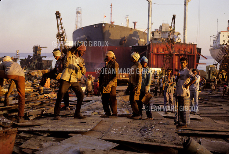 ALANG BEACH, GUJARAT, INDIA. JANUARY 15, 1993 : The Indian beach of Alang, is the largest ship wrecking yard in the world as dozens of the world's discarded ships can be seen in various stages of dismemberment along the 3 mile stretch sheltering over 80 scrap metal recycling companies. Workers come from all corners of India to find work in Alang. The labor is grueling, dangerous and intoxicating... 70 hours a week attacking giant tankers with acetylene torches, carrying tons of steel on their shoulders. (photo Jean-Marc Giboux)