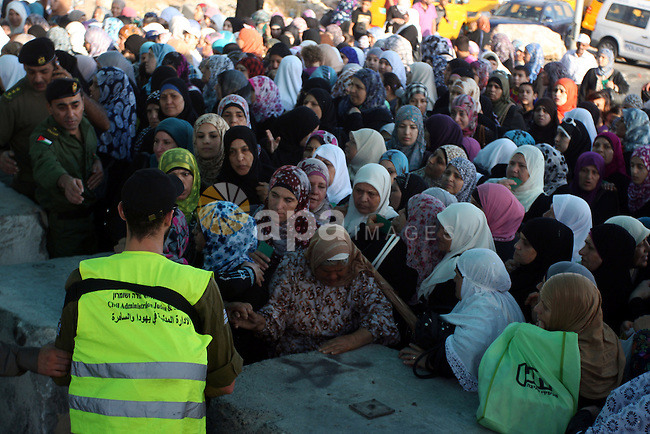 Palestinians wait to cross to Jerusalem from the Qalandia checkpoint near the West Bank city of Ramallah on Aug. 3, 2012. Palestinian Muslims are heading to Jerusalem to attend the third Friday prayers of the fasting month of Ramadan at the al-Aqsa mosque compound. Photo by Issam Rimawi