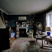 The spare bedroom is furnished with a lit bateau and the floor is covered with a large well-worn rug