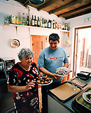GREECE, Patmos, Diakofti, Dodecanese Island,  Kostas and his mother Katerina Grillakis prepare food at their family taverna, Diakofti Taverna