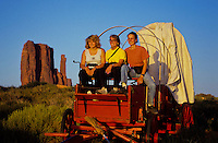 Three young girls on a horse wagon at sunrise in Monument Valley National Park and navaho Indian reservation,  Utah, USA