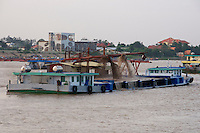 Phnom Penh, Cambodia. Sunset cruise to the confluence of Tonle Sap and Mekong river. Barges pumping up sand from the river ground for construction materials.
