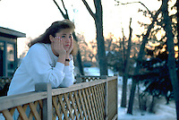 Teen age 17 with head in hands viewing winter sunset on deck.  Mound Minnesota USA