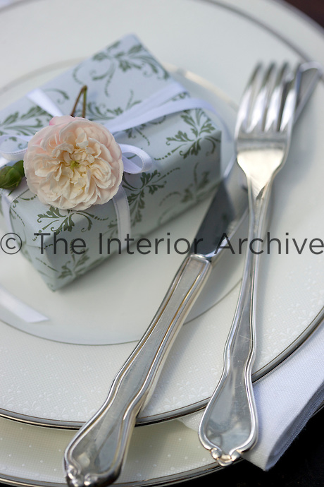 A box elegantly gift-wrapped in grey and silver topped with a pale pink rose is arranged on a place setting of silver and white