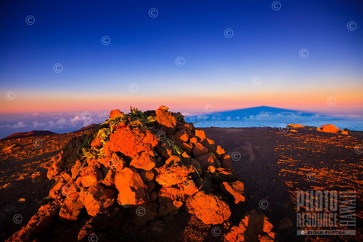 Sunset casts its light over offerings placed on a mound of rocks, Hawai'i Island.