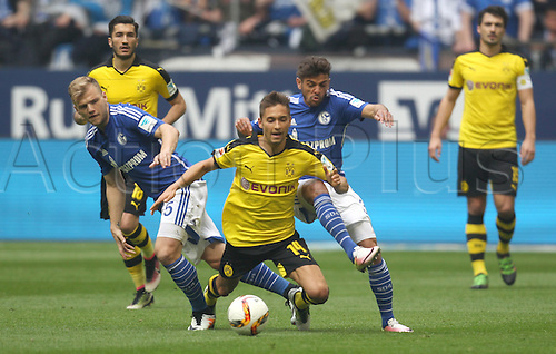 10.04.2016. Gelsenkirchen, Germany.  Schalke's Johannes Geis (L) and Junior Caicara (R) in action against Dortmund's Moritz Leitner during the German Bundesliga  match between FC Schalke 04 and Borussia Dortmund at the Veltins Arena in Gelsenkirchen, Germany, 10 April 2016.