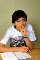 Cambodian American student age 17 thoughtfully making a journal entry.  St Paul Minnesota USA