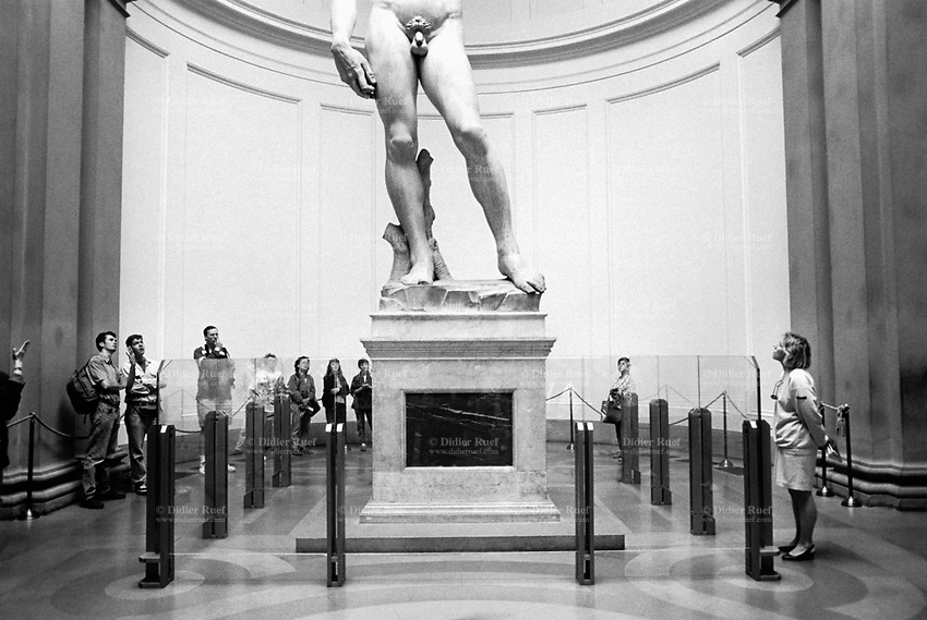"Italy. Tuscany region. Florence. The Galleria dell'Accademia di Firenze, or ""Gallery of the Academy of Florence"", is an art museum. David is a masterpiece of Renaissance sculpture created between 1501 and 1504, by the Italian artist Michelangelo. It is a 5.17-metre marble statue of a standing male nude. The statue represents the Biblical hero David, a favoured subject in the art of Florence. Originally commissioned as one of a series of statues of prophets to be positioned along the roofline of the east end of Florence Cathedral, the statue was placed instead in a public square, outside the Palazzo della Signoria, the seat of civic government in Florence, where it was unveiled on 8 September 1504. Because of the nature of the hero that it represented, it soon came to symbolize the defense of civil liberties embodied in the Florentine Republic, an independent city-state threatened on all sides by more powerful rival states and by the hegemony of the Medici family. The statue was moved to the Accademia Gallery in Florence in 1873, and later replaced at the original location by a replica. 10.04.93 © 1993 Didier Ruef"