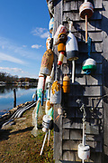 Lobster buoys hang from a shed at The John Hancock Warehouse and  Wharf located in York, Maine USA which is part of the New England seacoast.