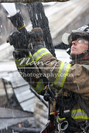 A firefighter extinguishing a fire with a hoseline.  Focus on the water spray