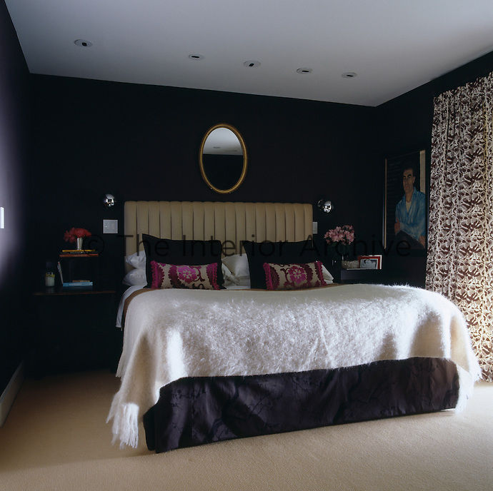 The small intimate bedroom has been decorated in dark colours