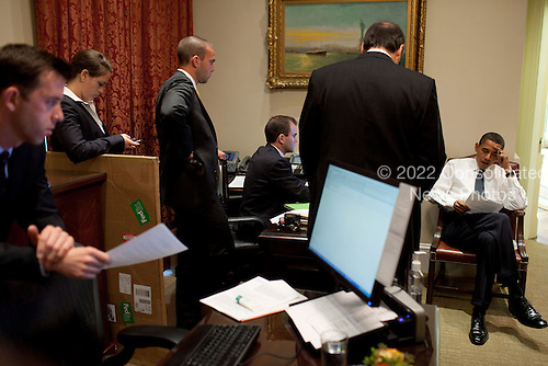 Washington, DC - October 8, 2009 -- United States President Barack Obama reads over his remarks regarding the 2009 Nobel Peace Prize with Senior Advisor David Axelrod and staff in the Outer Oval Office, October 9, 2009. .Mandatory Credit: Pete Souza - White House via CNP