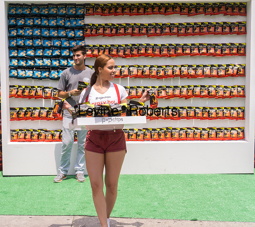 """Popchips promotes their """"Crazy Hot"""" flavor snack in Flatiron Plaza in New York on Wednesday, July 1, 2015. The snack company manufactures potato and corn chips using heat and pressure with no oil resulting in a less caloric, healthier snack. Various celebrities have endorsed and invested in the company including Ashton Kutcher and Katy Perry. (© Richard B. Levine)"""