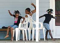 Anniya Martin, left, Conner Geffrard, center, and Ashanti Martin play musical chairs in the shade of a front porch Friday in Anderson.