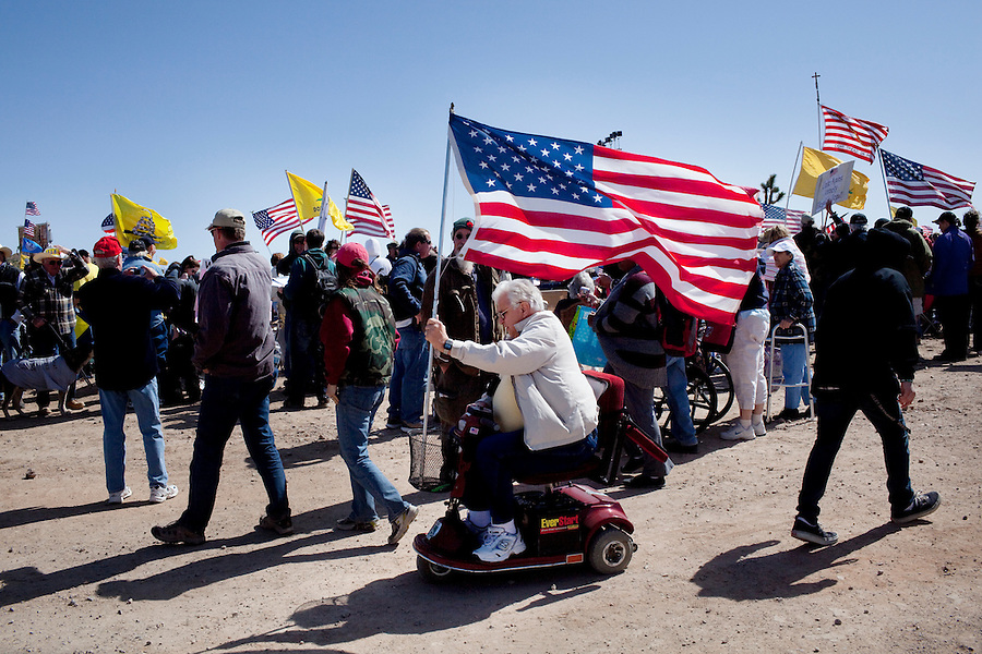 Searchlight, Nevada, March 28, 2010 - Dozens of Tea Party supporters carried flags to show their support during the first Tea Party Express rally in Searchlight, the hometown of Senate Majority Leader Harry Reid. Dubbed the Showdown in Searchlight, the event is located just north of town on private property near Reid's home. The raucous, but peaceful event was expected to draw 5,000 to 10,000 supporters, with actual estimates ranging from 7,000 to 8,000 - though party organizers said the numbers were as high as 13,000. The 20-day tour will wind through the United States ending up in Washington, D.C. on April 15 for a tax day rally. ...
