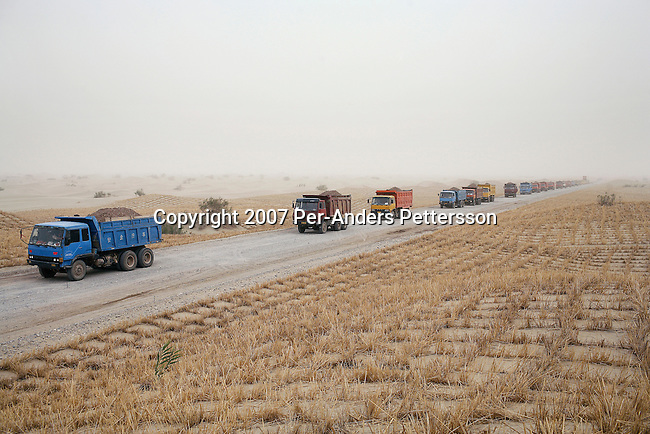 TAKLAMAKAN, CHINA - JUNE 16: Trucks line up with sand for the construction of the nearly completed Taklamakan desert highway on June 16, 2007 in Taklamakan Desert, China. The highway connects Aksu and Hetian of a distance of about 450 kilometers. The southern Silk Road route began in DunHuang and continued through the Taklamakan desert and to Khotan and Kashgar in the west. (Photo by Per-Anders Pettersson)..