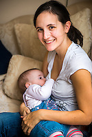 "A woman in her early twenties smiles at the camera while breastfeeding her nine month old baby girl at home. She is sitting on a sofa in her living room.<br /> <br /> Image from the breastfeeding collection of the ""We Do It In Public"" documentary photography picture library project: <br />  www.breastfeedinginpublic.co.uk<br /> <br /> <br /> Dorset, England, UK<br /> 08/03/2013<br /> <br /> © Paul Carter / wdiip.co.uk"