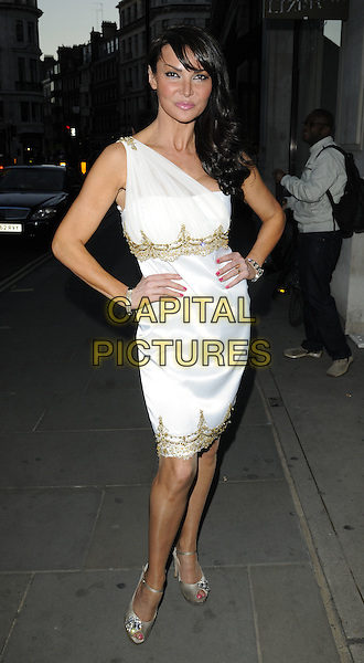 LIZZIE CUNDY  .'Recognise' magazine Launch Party at Swarovski Crystallized, London, England. .April 13th, 2010 .full length white dress hands on hips gold detail one shoulder trim silver peep toe shoes  .CAP/CAN.©Can Nguyen/Capital Pictures.
