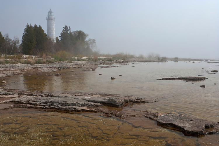 Foggy sunrise light on the Cana Island lighthouse on Lake Michigan; Door County, WI