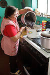 Guatemalan woman pours beans into a pot on the stove in her kitchen, Quetzaltenango, Guatemala