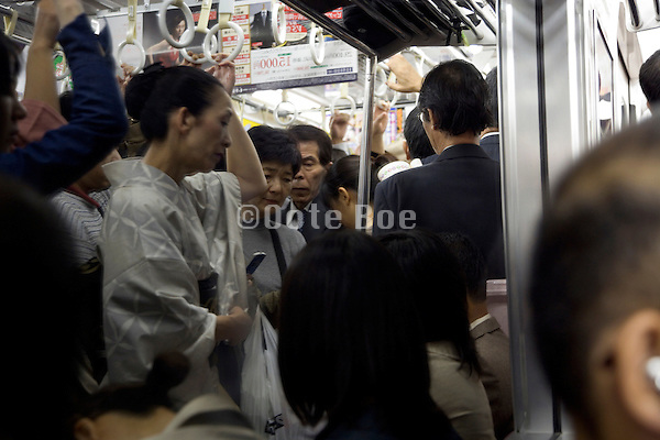 an woman in traditional Kimono dress standing in a full commuter train Japan