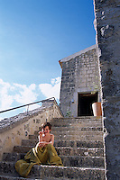 A boy sits on the sunny stone staircase leading up to the entrance to the chateau