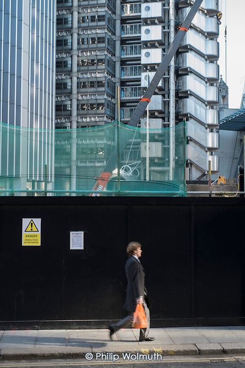 A City of London worker walks past a construction site next to the Lloyds Building.