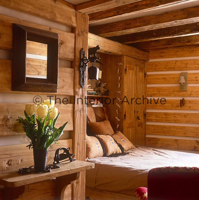 A cosy bedroom with a beamed ceiling and wood panelled walls. A double bed is set in a recess with a cupboard to one side.