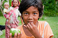 An Indonesian girl eating fruit as a part of a nutrition program.