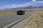 Black sedan car on highway leading into Great Sand Dunes National Park, Colorado. John offers private photo trips to Great Sand Dunes National Park and all of Colorado. All year long.