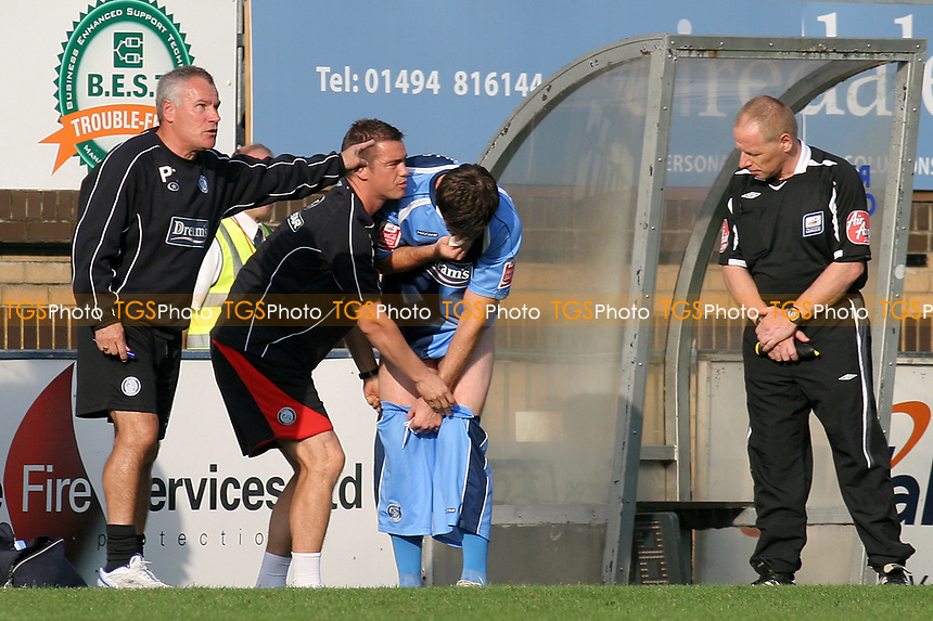 Sports Scientist Damien Doyle pulls up the shorts of Wycombe's Mike Williamson while he tries to stop his nose from bleeding during Wycombe Wanderers vs Dagenham & Redbridge, Coca Cola League Division Two Football at Adams Park on 20th September 2008