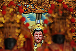 Bao-jhong Yi-min Temple, Kaohsiung -- Face of a Taoist god wedged between other statues.