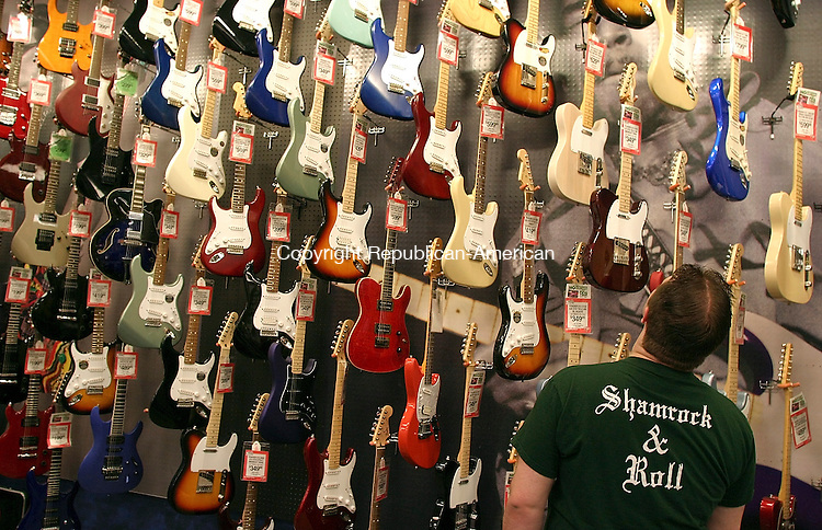 WATERBURY, CT - 23 March 2004 - 032304TH07 - Todd Marcin, a guitar player from Charleton, MA, stares up at the huge selection of guitars at the Guitar Center in Manchester Tuesday night.  He was in search of a new electric guitar.   TODD HOUGAS PHOTO