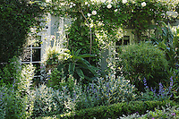 The herb parterre is enclosed by a low hedge of clipped box and overhung with white climbing roses