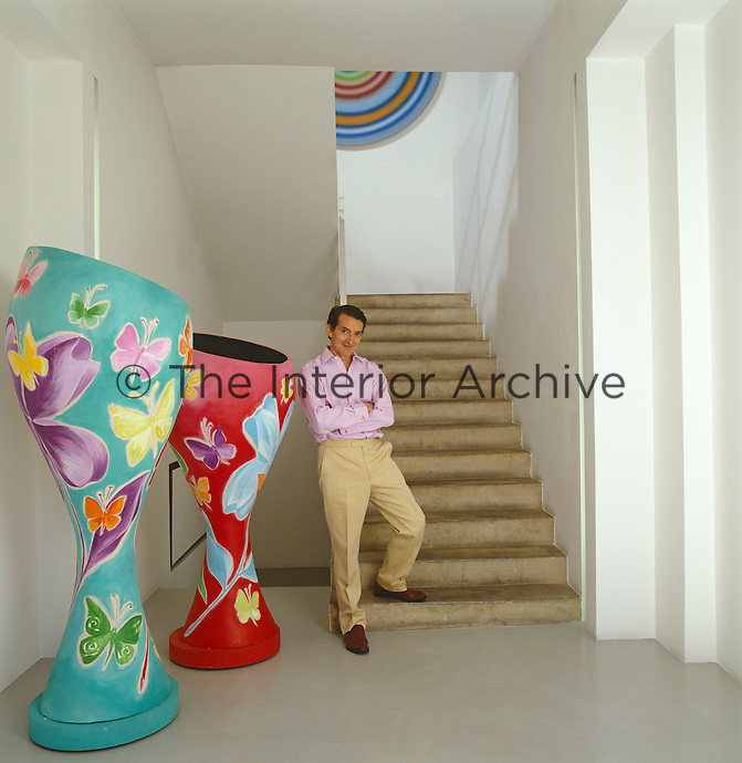 David Gill standing at the foot of a flight of stairs leading up to the converted handbag factory with a pair of Monumental vases by Grillo Demo in the entrance hall