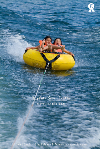 Two children (10-12 years) ridding in inflatable ring behind speed boat (Licence this image exclusively with Getty: http://www.gettyimages.com/detail/74583320 )