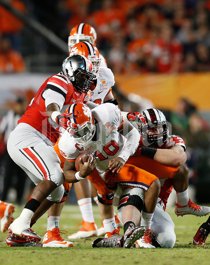 Clemson Tigers quarterback Tajh Boyd (10) gets sacked by Ohio State Buckeyes defensive lineman Joey Bosa (97) and Ohio State Buckeyes defensive lineman Adolphus Washington (92) in the third quarter of the Discover Orange Bowl between Ohio State and Clemson at Sun Life Stadium in Miami Gardens, Florida, Friday night, January 3, 2014. As of the fourth quarter the Ohio State Buckeyes led the Clemson Tigers 35 - 34.(The Columbus Dispatch / Eamon Queeney)