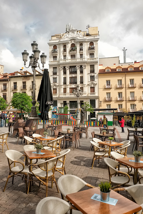 A quaint plaza filled with outside dining tables waits for today's visitors in the heart of Madrid.