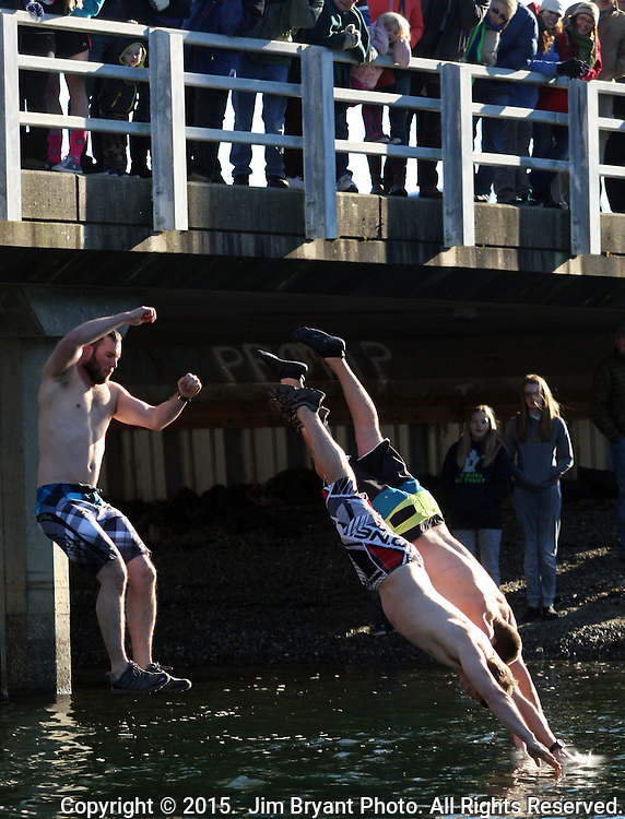 Three jumpers dive and leap off the bridge into the Burley Lagoon during the 31st annual Polar Bear on January 1, 2015 in Olalla, Washington. Over 500 hardy participants joined in on the New Year's Day Tradition by jumping into the chilly lagoon waters during the annual Polar Bear Plunge. ©2015.  Jim Bryant Photo. All Rights Reserved.