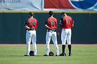 (L-R) Hickory Crawdads outfielders Tanner Gardner (27), Miguel Aparicio (5), and Jose Almonte (9) stand for the National Anthem prior to the game against the Charleston RiverDogs at L.P. Frans Stadium on May 13, 2019 in Hickory, North Carolina. The Crawdads defeated the RiverDogs 7-5. (Brian Westerholt/Four Seam Images)