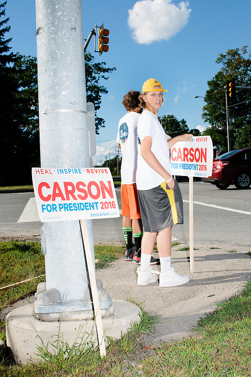 Teenagers hold signs toward traffic for Republican presidential candidate Dr. Ben Carson at Londonderry Old Home Day in Londonderry, New Hampshire. Carson later showed up at the event to meet New Hampshire voters.