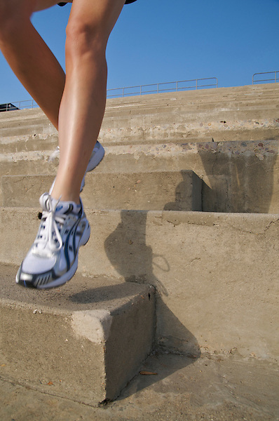 A woman's legs running down concrete steps while training.