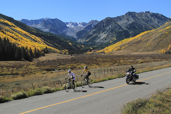 Man and woman biking and Harley-Davidson motorcycle rider on Castle Creek Road, Aspen, Colorado. .  John offers private photo tours in Denver, Boulder and throughout Colorado. Year-round.
