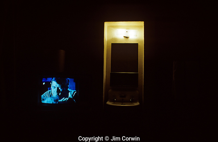 Hotel room at night with tv on and man drinking downtown Seattle Washington State uSA