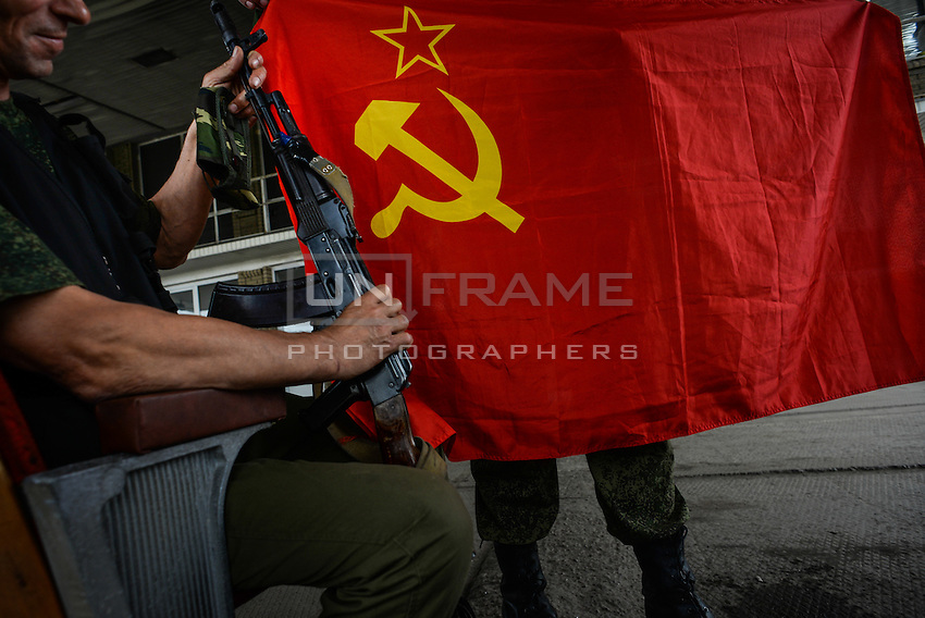 Insurgents unfold USSR flag at the border crossing between Ukraine and Russia at Izvarine check point - one of border crossings controlled by Luhansk Peoples Republic.